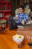Hombre joven que ríe y que mira la sentada del smartphone Foto de archivo libre de regalías