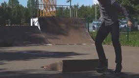 Hombre joven que realiza un truco con su monopatín en parque del patín Deporte, concepto activo de la vida almacen de video