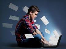Hombre joven que recibe toneladas de mensajes en el ordenador portátil Imagen de archivo libre de regalías