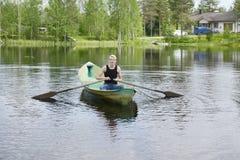 Hombre joven que rema un barco en un lago Imagenes de archivo