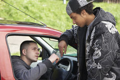 Hombre joven que reparte las drogas del coche Foto de archivo