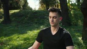 Hombre joven que respira profundamente con Forest In The Background verde Yoga de la pr?ctica en el parque en una manta que mient almacen de video