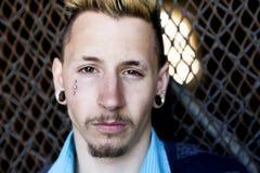Hombre joven que revela su tristeza y depresión contra una cerca de la alambrada Fotos de archivo libres de regalías