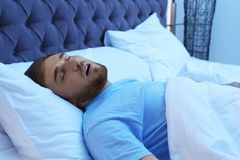 Hombre joven que ronca mientras que duerme en cama en la noche fotos de archivo