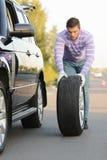 Hombre joven que rueda una rueda de repuesto Foto de archivo libre de regalías