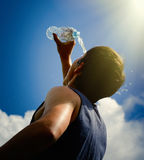 Hombre joven que salpica y que vierte el agua dulce de una botella en su cabeza Foto de archivo