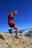 Hombre joven que salta abajo de rocas en una montaña Foto de archivo libre de regalías
