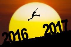 Hombre joven que salta con el número 2016 y 2017 Imagen de archivo libre de regalías