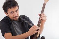 Hombre joven que salta con la guitarra eléctrica Foto de archivo