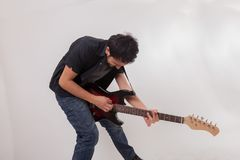 Hombre joven que salta con la guitarra eléctrica Imagen de archivo