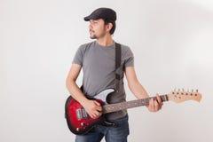Hombre joven que salta con la guitarra eléctrica Foto de archivo libre de regalías