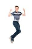 Hombre joven que salta con los pulgares aumentados para arriba. Fotografía de archivo libre de regalías