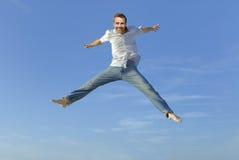 Hombre joven que salta en el aire Foto de archivo libre de regalías