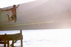 Hombre joven que salta en el lago Fotos de archivo