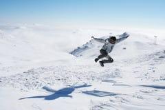 Hombre joven que salta en la nieve para la diversión Imagenes de archivo