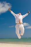 Hombre joven que salta en la playa Imagenes de archivo