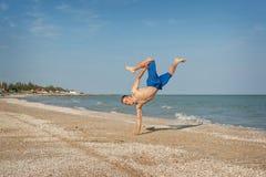 Hombre joven que salta en la playa Foto de archivo libre de regalías