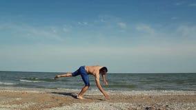 Hombre joven que salta en la playa almacen de video
