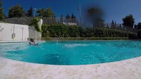 Hombre joven que salta en piscina clara azul metrajes