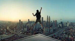 Hombre joven que salta en tejado con la gran opinión de la salida del sol del paisaje urbano imagenes de archivo
