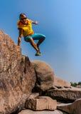 Hombre joven que salta entre las rocas Foto de archivo libre de regalías