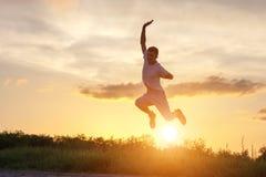 Hombre joven que salta para arriba contra el cielo de la puesta del sol fotos de archivo