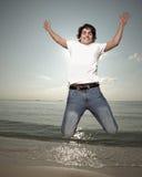 Hombre joven que salta por la orilla de mar Imagen de archivo libre de regalías