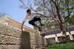 Hombre joven que salta sobre una cerca Foto de archivo libre de regalías