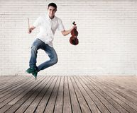 Hombre joven que salta y que sostiene un violín Imágenes de archivo libres de regalías