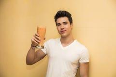 Hombre joven que saluda con una bebida sana Imagen de archivo libre de regalías
