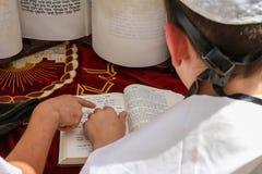 Hombre joven que señala en un libro de la biblia, mientras que lee una rogación Foto de archivo libre de regalías