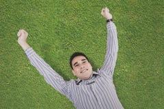 Hombre joven que se acuesta en la hierba Imagen de archivo