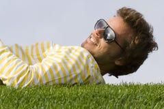 Hombre joven que se acuesta en la hierba Imagen de archivo libre de regalías