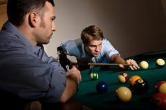Hombre joven que se centra en jugar el billar Imagen de archivo libre de regalías