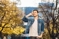 Hombre joven que se coloca al aire libre, hablando en el teléfono foto de archivo libre de regalías