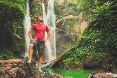 Hombre joven que se coloca cerca de una cascada en bosque Fotos de archivo libres de regalías