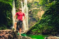 Hombre joven que se coloca cerca de una cascada en bosque Foto de archivo libre de regalías