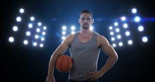 Hombre joven que se coloca con el baloncesto almacen de video