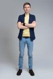 Hombre joven que se coloca con sus brazos cruzados Fotografía de archivo