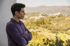 Hombre joven que se coloca de mirada sobre un paisaje rural Fotos de archivo libres de regalías