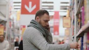 Hombre joven que se coloca delante de estantes del supermercado, llevando a cabo el teléfono y la llamada Toma el artículo y cons metrajes