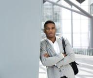 Hombre joven que se coloca en aeropuerto con el bolso Imagenes de archivo