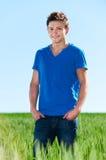Hombre joven que se coloca en campo verde Fotografía de archivo