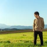 Hombre joven que se coloca en campo verde. Imagenes de archivo