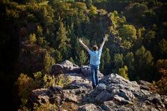 Hombre joven que se coloca en cuesta de la roca Foto de archivo libre de regalías