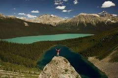 Hombre joven que se coloca en el canto rodado sobre los lagos Imagen de archivo libre de regalías