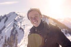 Hombre joven que se coloca en el sol rodeado por las montañas nevosas Fotos de archivo libres de regalías