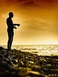 Hombre joven que se coloca en la arena mojada en la puesta del sol brillante Imagen de archivo