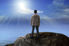 Hombre joven que se coloca en la montaña de la roca y que mira al sol Foto de archivo libre de regalías