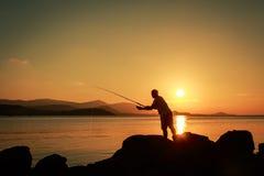 Hombre joven que se coloca en piedra y la pesca Imagen de archivo libre de regalías